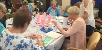 Ladies decorating cakes in the day services unit